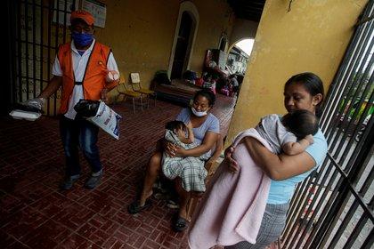 Mujeres cargan a sus bebés en una escuela que se utiliza como refugio a medida que se acerca la tormenta Iota, en Choluteca, Honduras. REUTERS/Jorge Cabrera