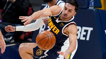 Denver Nuggets guard Facundo Campazzo, front, loses control of the ball as Utah Jazz guard Mike Conley defends in the first half of an NBA basketball game Sunday, Jan. 17, 2021, in Denver. (AP Photo/David Zalubowski)