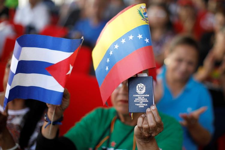 Un seguidor de Nicolás Maduro con una copia de la constitución venezolana y las banderas de Venezuela y Cuba (REUTERS / Carlos Garcia Rawlins)