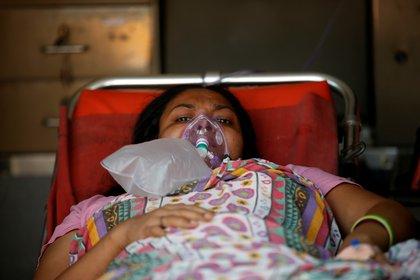 Una paciente con un problema respiratorio usa una máscara de oxígeno mientras yace dentro de una ambulancia esperando en una fila para ingresar a un hospital COVID-19, en medio de la pandemia de la enfermedad por coronavirus, Ahmedabad, India, 14 de abril de 2021. REUTERS / Amit Dave