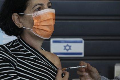 Una mujer israelí recibe una vacuna contra el coronavirus de Pfizer-BioNTech en un centro de vacunación en Tel Aviv, Israel, el martes 2 de febrero de 2021. (AP Photo/Sebastian Scheiner)