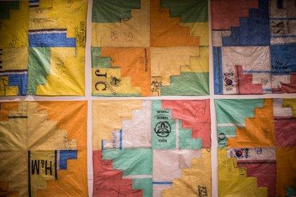 """Los tapices están realizados con bolsa arpillera, que se utiliza para trasladar la ropa deshechada, y llevan las """"firmas"""" de feriantes como de las marcas que se copian o crean"""