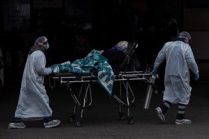 Trabajadores del Servicio de Atención Médico de Urgencias (SAMU) y del Hospital San José trasladan a un paciente al servicio de urgencias para adultos, el cual ya se encuentra colapsado ante el aumento de casos por la COVID-19, en Santiago (Chile). (EFE/Alberto Valdés)