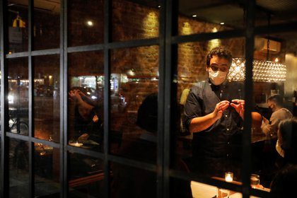 A person serves customers at Oiji, a restaurant in the East Village as new restrictions were announced on bars and restaurants for 10 PM closure, to help fight the spread of the coronavirus disease (COVID-19), in Manhattan, New York City November 13, 2020. REUTERS/Andrew Kelly