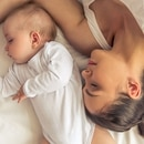 Top view of beautiful young mom and her cute little baby sleeping in bed at home