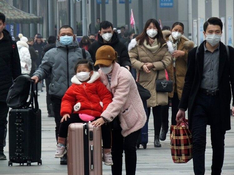 Viajeros llevan máscaras cuando salen de una estación de tren en Yichang, en la provincia de Hubei, en el sur de China, el martes 21 de enero de 2020 (Chinatopix via AP)