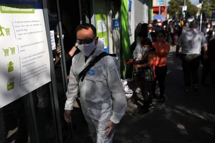 Un hombre usa un traje de protección a la espera de entrar a un supermercado en Santiago de Chile (Reuters)