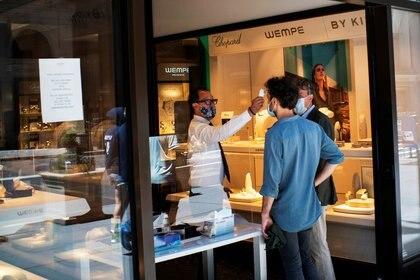 FOTO DE ARCHIVO: Un trabajador chequea la temperatura de un cliente en un local en Nueva York, EEUU, 12 de junio del 2020. REUTERS/Eduardo Munoz