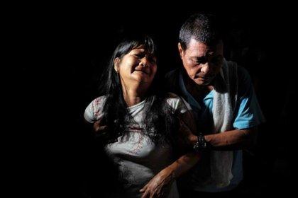 Néstor Hilbano consuela a su mujer, Alma, después de que ambos hayan visto el cadáver de su hijo en una bolsa en un callejón oscuro de Tatalon. Richard Hilbano, de 32 años, fue abatido por la policía en una redada antidrogas. Los agentes declararon que Richard estaba fumando marihuana con otras tres personas y los mataron a todos. JES AZNAR