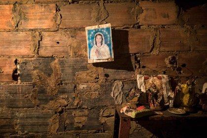 Una imagen de la Virgen María cuelga de una pared de ladrillos al lado de la habitación donde se prepara el cadáver de Teresa Jiménez después de su muerte por causas naturales a la edad de 91 años en Maracaibo, Venezuela, el 17 de noviembre de 2019 (AP)