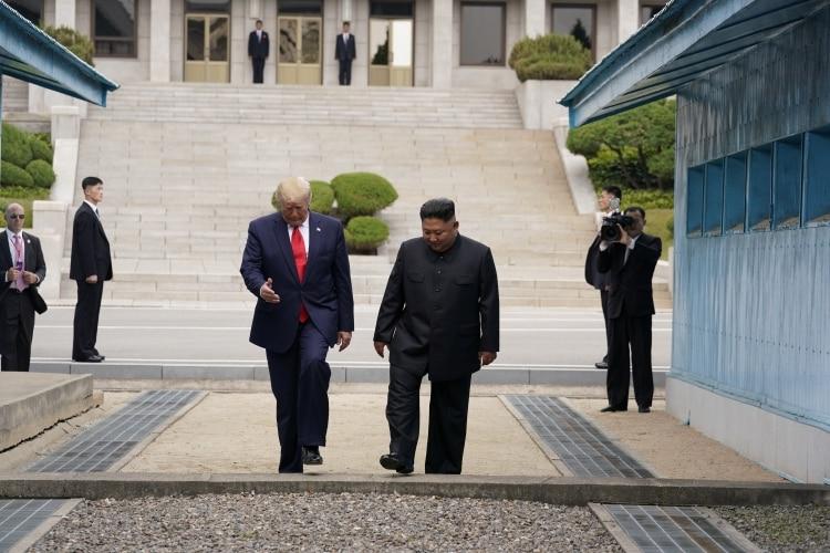 Donald Trumpy Kim Jong-un cruzan al lado surcoreano. (REUTERS/Kevin Lamarque)