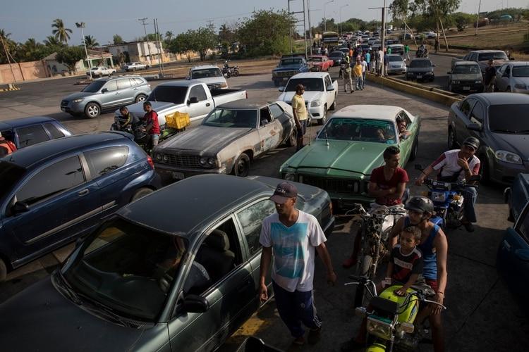 En plena crisis económica, muchos venezolanos se ven obligados a dejar de trabajar un día para conseguir llenar un tanque (AP)