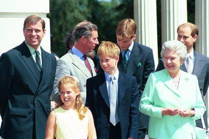 El príncipe Andrew con su hija Beatrice, su madre, la reina Isabel, su hermano el príncipe Carlos y parte de la Familia Real, en agosto de 1998 (Shutterstock)