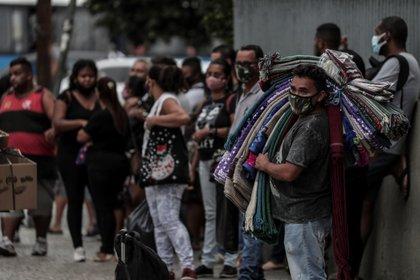 Decenas de personas esperan un autobús, en la ciudad de Río de Janeiro (EFE/Antonio Lacerda/Archivo)