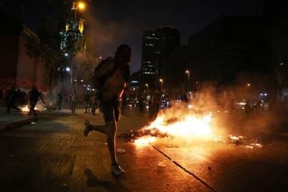 Manifestantes pasan frente a una barricada durante una protesta en Santiago, Chile. Marzo 13, 2020. REUTERS/Iván Alvarado