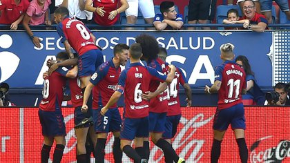 Osasuna's Spanish midfielder Roberto Torres (L) celebrates with teammates after scoring a goal during the Spanish league football match CA Osasuna against FC Barcelona at El Sadar stadium in Pamplona on August 31, on 2019. (Photo by ANDER GILLENEA / AFP)