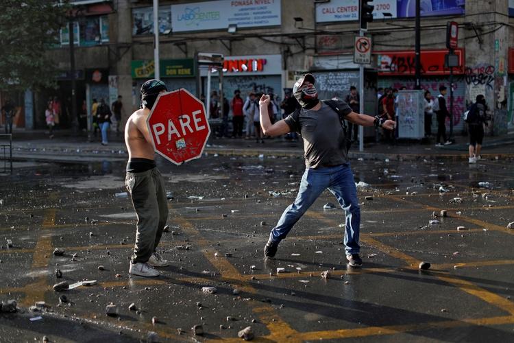 Un manifestante utiliza una señal de alto como protección mientras otro lanza piedras durante una protesta contra el gobierno el 29 de octubre de 2019 (REUTERS/Jorge Silva/File Photo)