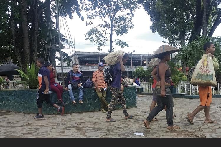 Hombres y mujeres cruzan la plaza Bolívar de El Callao rumbo a los yacimientos. Foto: Lorena Meléndez