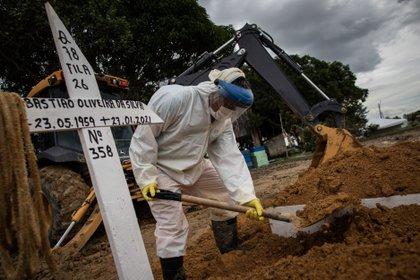 Trabajadores entierran a una persona fallecida por covid-19, en el cementerio público Nossa Senhora Aparecida en Manaos, Amazonas (Brasil). EFE /RAPHAEL ALVES/Archivo