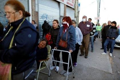 Jubilados y personas con planes de asistencia social hacen cola fuera de un banco. Buenos Aires, Argentina, 3 de abril de 2020. REUTERS / Agustin Marcarian