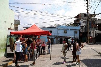 Miembros del partido socialista venezolano toman la temperatura de una mujer en un puesto de control en la barriada de Catia durante una cuarentena a nivel nacional debido al brote de COVID-19 en Caracas. 15 abril 2020. REUTERS/Manaure Quintero