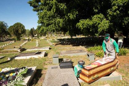 Trabajadores del cementerio Campo de Esperanza entierran una víctima de coronavirus. EFE/ Joédson Alves