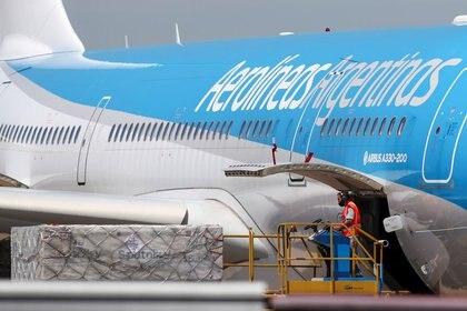 Un trabajador descarga contenedores refrigerantes con dosis de la vacuna Sputnik V (Gam-COVID-Vac) contra la enfermedad por coronavirus (COVID-19), en el Aeropuerto Internacional Ezeiza de Buenos Aires, Argentina, 24 de diciembre de 2020. REUTERS/Agustin Marcarian