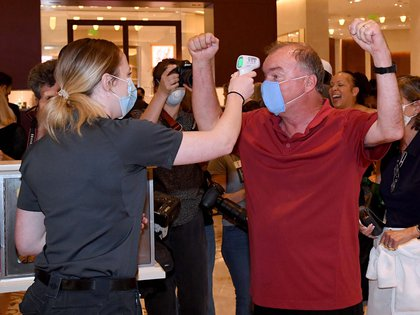 LAS VEGAS, NEVADA - JUNE 04: Jay McAvoy (R) of Colorado cheers as an employee takes his temperature as he arrives at Bellagio Resort & Casino on the Las Vegas Strip just after the property opened for the first time since being closed on March 17 because of the coronavirus (COVID-19) pandemic on June 4, 2020 in Las Vegas, Nevada. Hotel-casinos throughout the state are opening today as part of a phased reopening of the economy with social distancing guidelines and other restrictions in place. MGM Resorts International reopened Bellagio, New York-New York Hotel & Casino, MGM Grand Hotel & Casino and The Signature today.   Ethan Miller/Getty Images/AFP