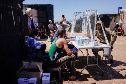 Miembros de la ONG española Médicos del Mundo prestan atención médica a un migrante de Marruecos en un barrio de chabolas conocido como El Hoyo, durante el brote de la enfermedad coronavírica (COVID-19) en Níjar, en la región de Almería, España, el 29 de abril de 2020. Foto tomada el 29 de abril de 2020. (REUTERS/Juan Medina)