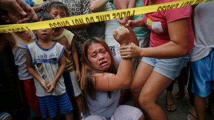 Janeth Mejos observa cómo el cuerpo de su padre, Paquito, muerto a tiros en una operación policial, es llevado desde su casa de Manila. La policía dice haber matado a más de 2.000 sospechosos, en su mayoría en legítima defensa, desde que comenzó la guerra contra las drogas. Pero algunas familias en duelo han dicho a Reuters que sus seres queridos estaban desarmados y pidiendo misericordia cuando la policía abrió fuego (Reuters)