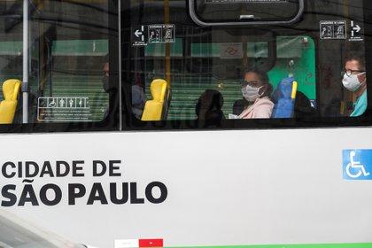 Personas con barbijo en un bus (EFE/Sebastião Moreira)