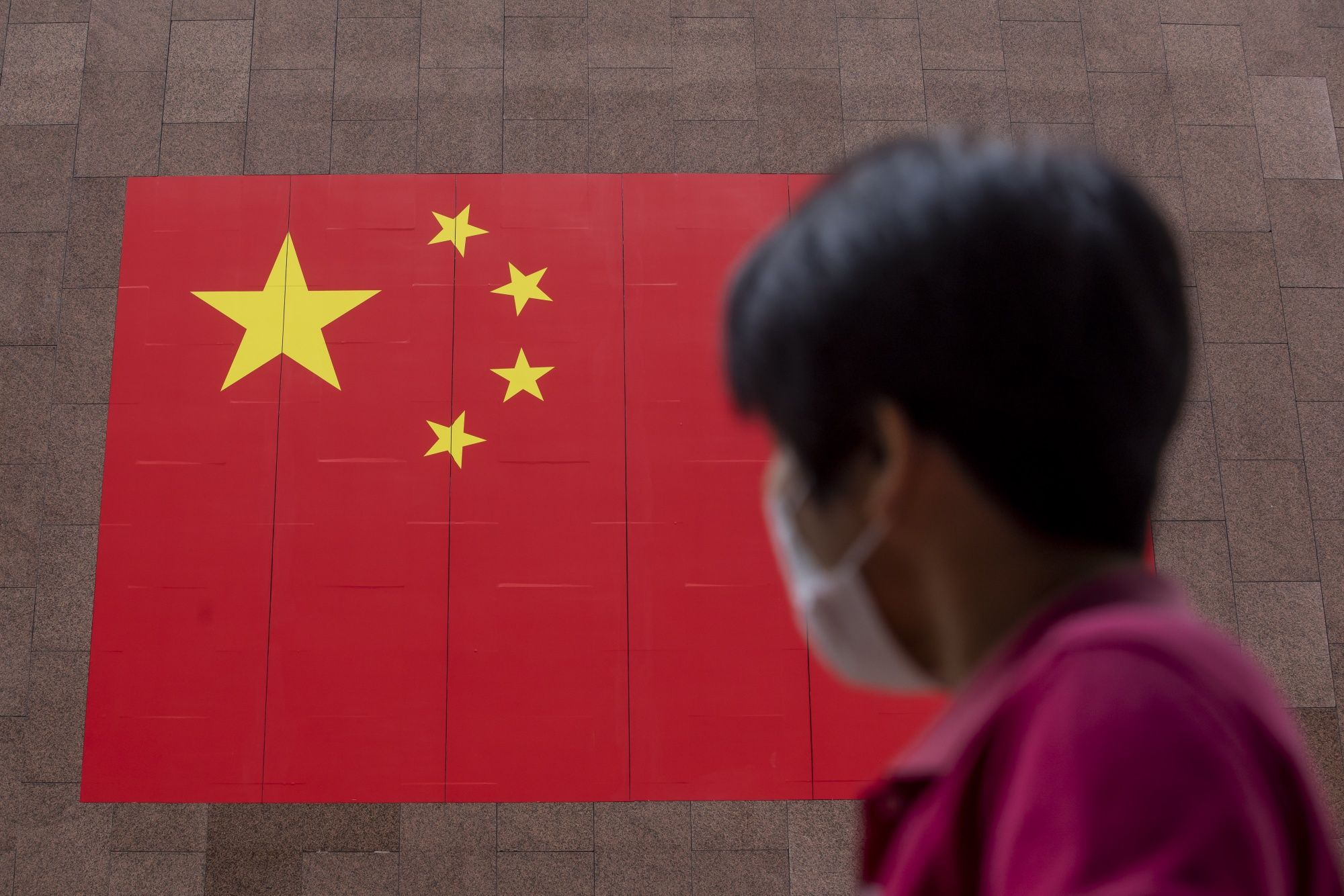 A pedestrian wearing a protective mask walks past a Chinese national flag displayed outside a hotel on National Day in Hong Kong, China, on Thursday, Oct. 1, 2020. Hong Kong leader Carrie Lam declared a return of stability, even as authorities deployed thousands of riot police and threats of arrests to deter protesters from returning to the streets in the Asian financial center. Photographer: Paul Yeung/Bloomberg
