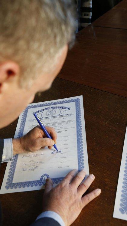 Un elector firma un acta confirmando su voto por Donald Trump en Michigan (Fotógrafo: Jeff Kowalsky/Bloomberg)