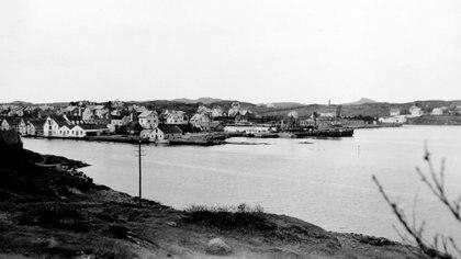 """El puerto de Kopervik en la isla de Karmoy fue el objetivo de la Operación Checkmate. En el centro de la escena, el barreminas que quedó escorado tras el ataque del comando británico. Hay versiones que aseguran que la incursión hundió varias embarcaciones, según la información de un documento alemán que cita """"varios barcos de vapor alemanes fueron hundidos en Oslo y Kopervik, faltan detalles"""""""