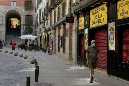 FILE PHOTO: A man wearing a protective mask walks past a closed bar, amid the coronavirus disease (COVID-19) outbreak, in Madrid, Spain, July 31, 2020. REUTERS/Javier Barbancho
