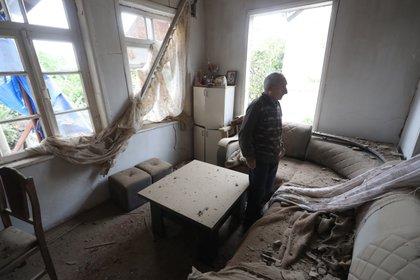 Un hombre armenio permanece de pie entre los escombros de su hogar en la ciudad de Martuini, en la autoproclamada república de Nagorno Karabaj.EFE/ Vahram Baghdasaryan