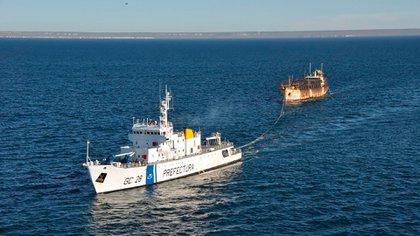 Buque guardacostas remolcando a pesquero infractor para dar inicio a las actuaciones legales respectivas en puerto