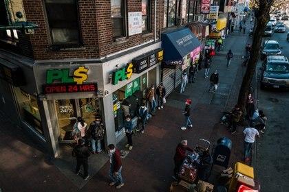 Una larga fila de personas con tapabocas esperan ingresar a PLS, un negocio de transferencias electrónicas y cambio de cheques en Jackson Heights, Queens. (Ryan Christopher Jones / The New York Times)