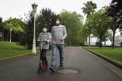 Un enfant voyage avec un scooter avec un adulte le premier jour où les enfants de moins de 14 ans peuvent sortir à Bilbao.  H.Bilbao - Europa Press