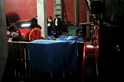 Personal de emergencia permanece en una morgue improvisada por la compañía de Bomberos Voluntarios de Alotenango (Guatemala) donde se encuentran los cuerpos de los siete fallecidos que ha dejado la erupción del Volcán de Fuego (EFE/ Esteban Biba)