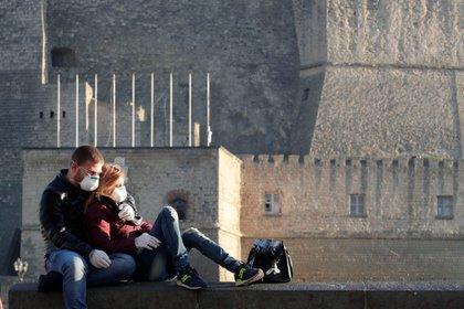 Una pareja con máscaras protectoras toma algo de sol en Nápoles en plena pandemia de coronavirus (Reuters)