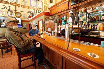 Fotografía de archivo del 21 de mayo de 2020 que muestra a clientes en un bar durante la fase 2 de reapertura de restaurantes en Napa, California, Estados Unidos (EFE/ John G. Mabanglo/ archivo)