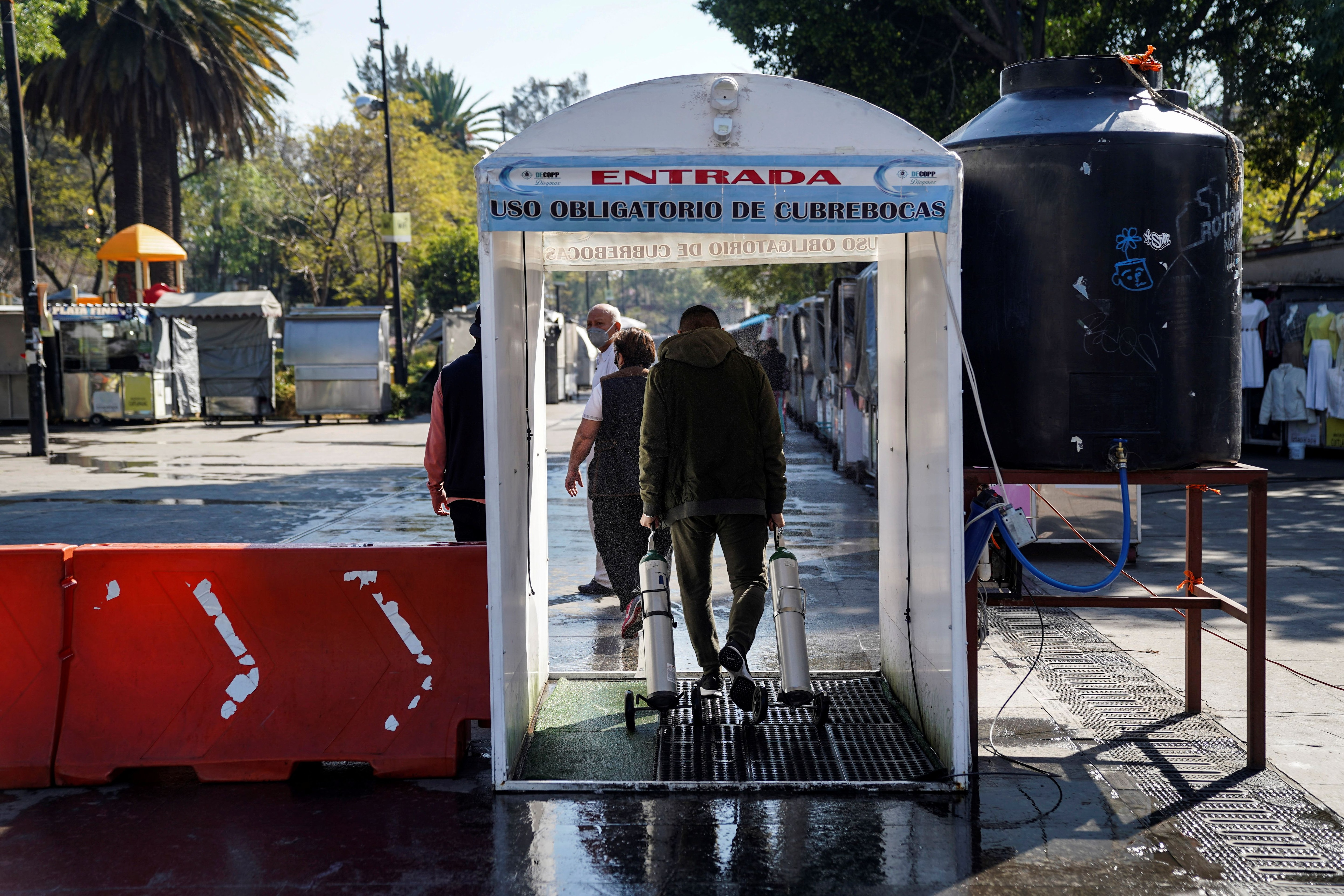 A man walks through a disinfection chamber while carrying oxygen tanks for his relatives infected with the coronavirus disease, as part of a city government's free recharge program, in the municipality of Iztapalapa, in Mexico City, Mexico 18 January 2021.