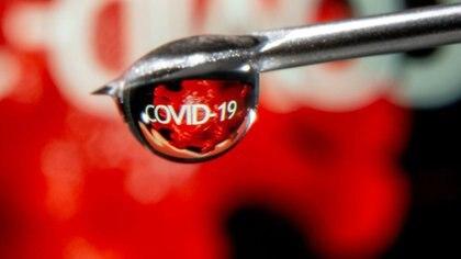 """Imagen de archivo ilustrativa de la palabra """"COVID-19"""" reflejada en una gota en la aguja de una jeringa, tomada el 9 de noviembre, 2020. REUTERS/Dado Ruvic/Ilustración/Archivo"""
