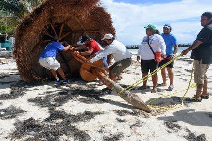 Empleados de Puerto Morelos, en Quintana Roo, retiran sombrillas de la playa para evitar que las arrastre el viento del huracán Delta (Foto: Elizabeth Ruiz/AFP)