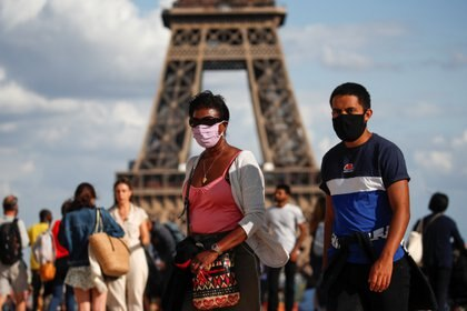People wearing protective face masks walk at the Trocadero square near the Eiffel Tower in Paris as France reinforces mask-wearing as part of efforts to curb a resurgence of the coronavirus disease (COVID-19) across the country, August 3, 2020. REUTERS/Gonzalo Fuentes
