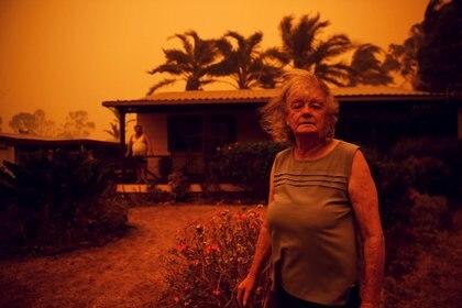 Nancy Allen y Brian Allen se detienen afuera de su casa mientras los fuertes vientos empujan humo y cenizas del Currowan Fire hacia Nowra, New South Wales, Australia, el 4 de enero de 2020. El cielo naranja tiñe toda la geografía del país (Reuters)