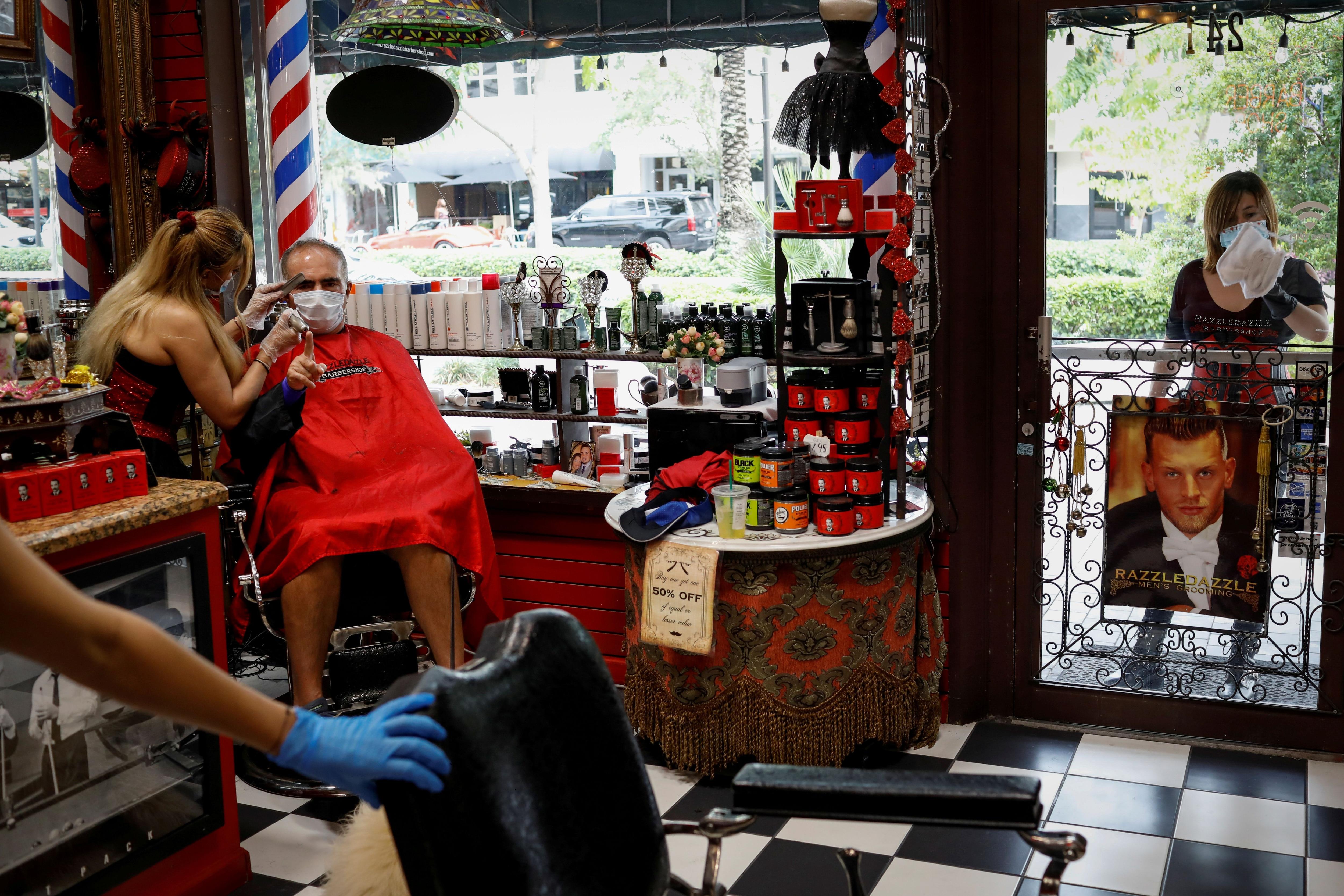 Aunque se hayan vacunados completamente, las personas deben seguir yendo con barbijo o mascarilla a la peluquería, al restaurant o al cine, entre otros lugares cerrados. Es porque aún hay chances de contagiarse y de contagiar el coronavirus, aunque la vacuna baja el riesgo de desarrollar cuadros graves / REUTERS/Marco Bello