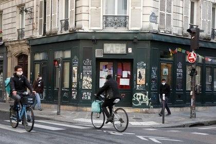 Ciclistas pasan por delante del bar Au Chat Noir cerrado como parte de las restricciones más estrictas debido al brote de la enfermedad coronavirus (COVID-19) en París, Francia, el 13 de octubre de 2020 (REUTERS/Charles Platiau)