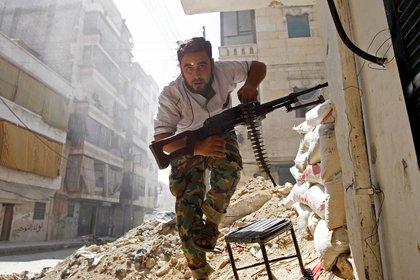 Un miliciano del Ejército Sirio de Liberación se cubre durante los combates contra el Ejército de Al Assad